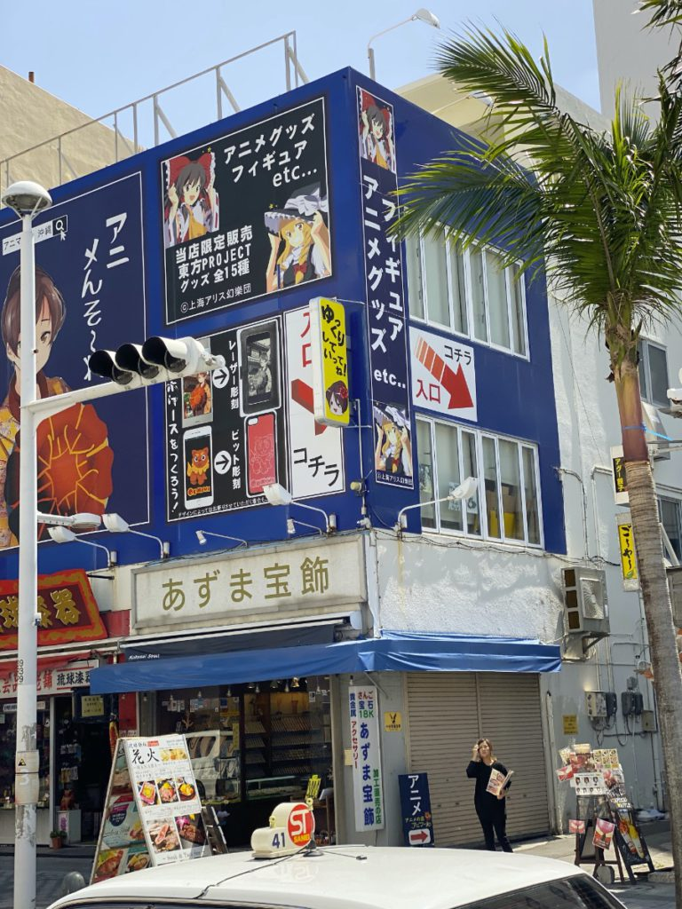 A side view of the Anima-ru anime store sign showing arrows pointing down an alley